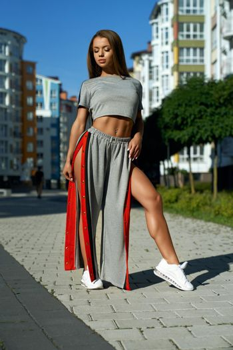 Fashionable sporty woman posing near multistorey buildings.