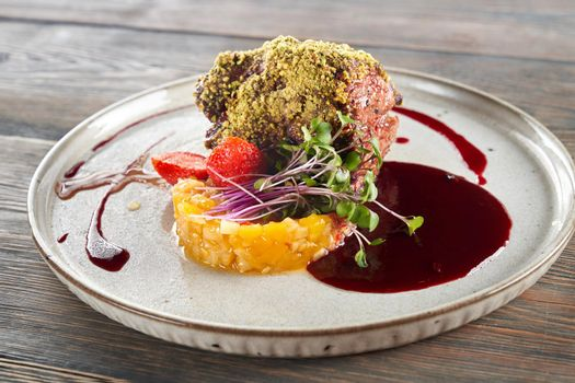 Beef with pistachio topping served with fruits and berries.