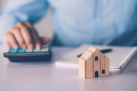 Hand of businessman planning and calculate expense and mortgage with calculator and home on desk, insurance and budget of residential, examining of loan and residence, business and property concept.