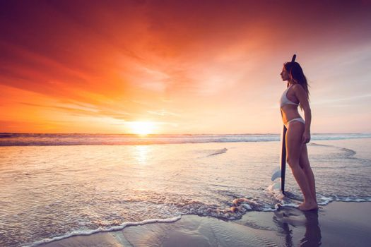 Woman holding surfboard at sunset