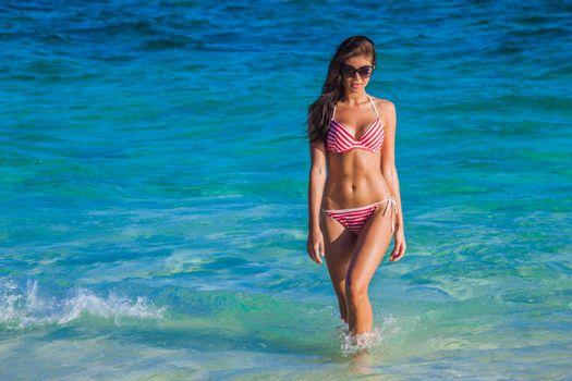 Woman in swimsuit walking on the beach