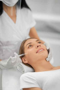 Smiling woman doing procedure for tighten skin.