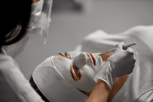 Beautician doing special beauty procedure for patient.