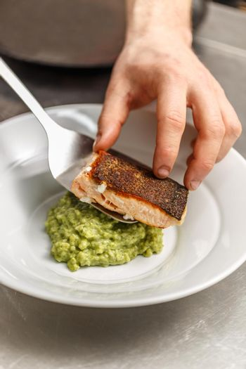 Chef is serving grilled salmon