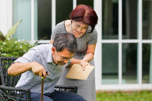 Wife holding senior adult husban , weak muscle.