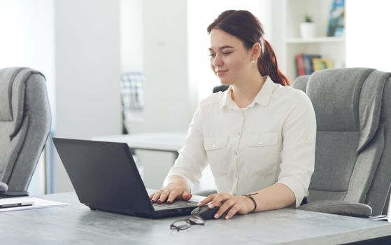 Young attractive business woman working in office smiling looking into laptop