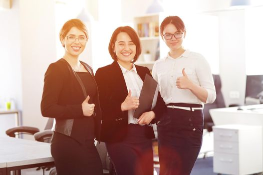 Three young successful business women in the office smiling happily