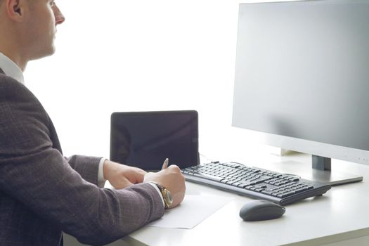 Young business man working at the computer and papers on the table
