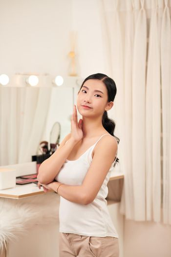 Attractive Vietnamese woman looking at her face in the mirror