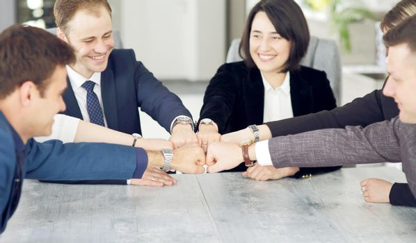 Unity and teamwork concept of young business people folding their hands together