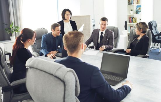 Group of young successful businessmen lawyers communicating together in a conference room while working on a project