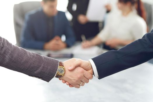 Business people shaking hands finishing a meeting in the background of their work team
