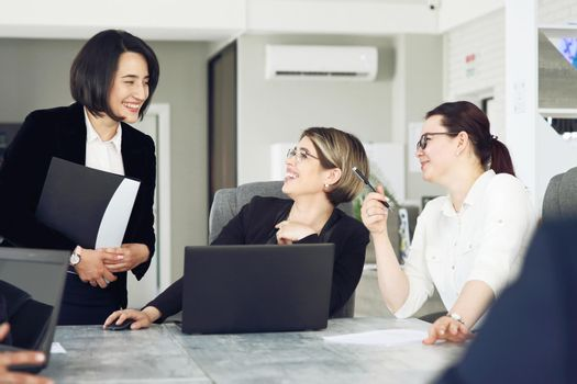 Three young successful business women in the office, together, happily working on a project