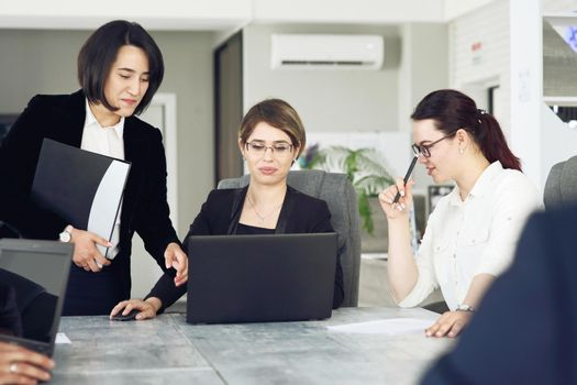 Three young successful business women in the office working together on a project