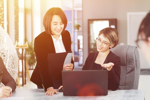 Two young business women in the office, analyzing information looking into a laptop and smiling