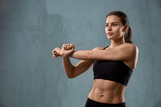 Flexible fitnesswoman stretching arm before training.