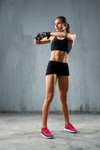 Flexible fitnesswoman stretching arms before training.