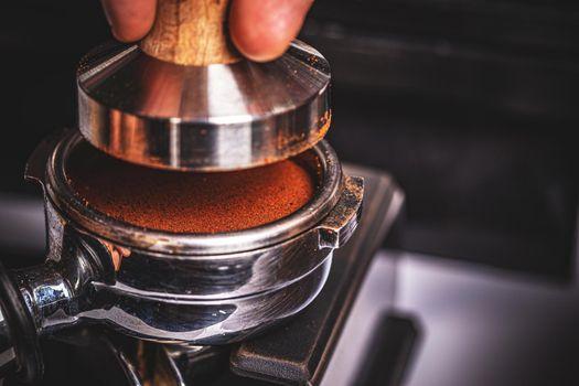 Barista pressing ground coffee