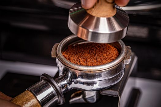 Barista is using a tamper