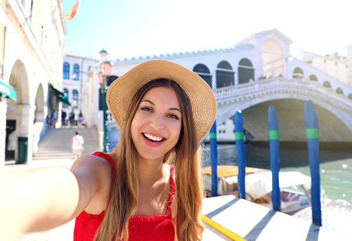 Venice tourist girl on summer holidays taking selfie photo with famous Rialto Bridge. Venice tourist attraction in Italy.