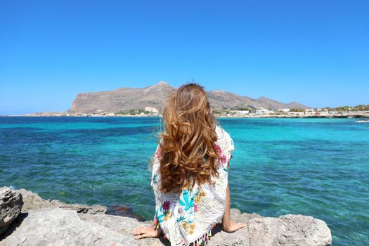 Beautiful girl enjoying the breeze at the beach in Favignana, Sicily