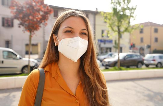 Portrait of young woman in city street wearing KN95 FFP2 mask protective for spreading of disease virus SARS-CoV-2. Girl with protective mask on face against Coronavirus Disease 2019.