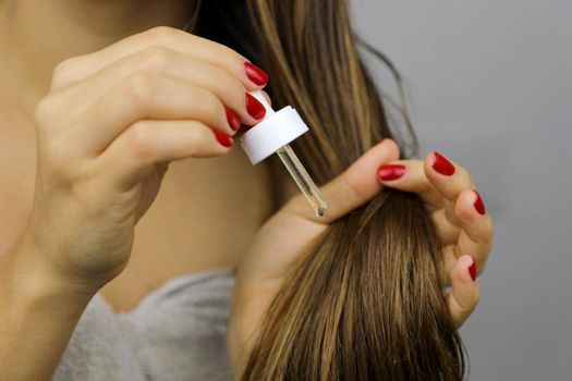 Woman applying oil on dry hair or sun protection concept. Split hair tips. Oiling hair before washing. Hair care concept.