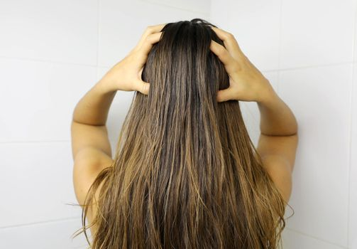 Young woman applying hair oil with her fingers. Oiling hair before washing. Hair care concept.