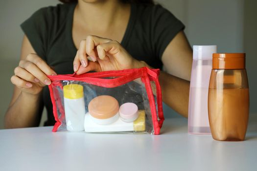 Woman prepare travel kit for transporting cosmetics on airplane