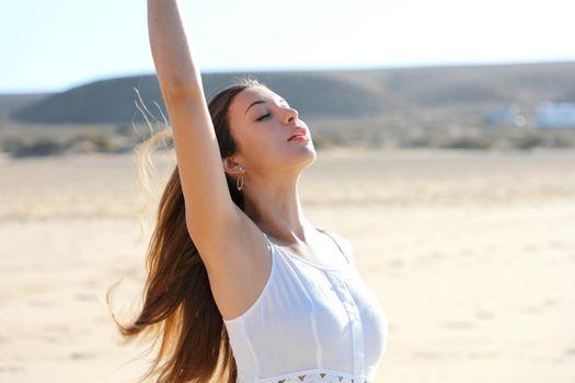 Beautiful woman taking deep breath enjoying fresh air on the beach