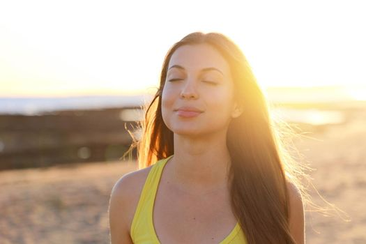 Backlight portrait of a woman breathing deep fresh air in the morning sunrise on the beach
