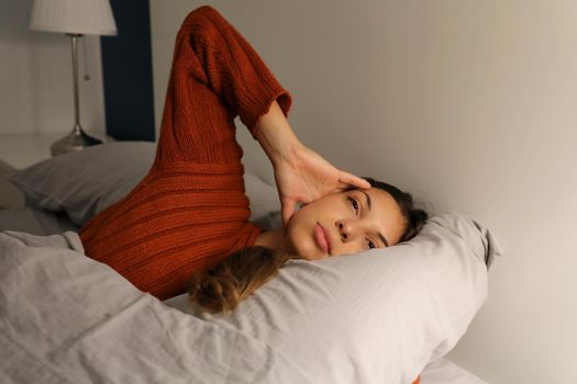 Young woman on bed suffering headache insomnia for migraine stress