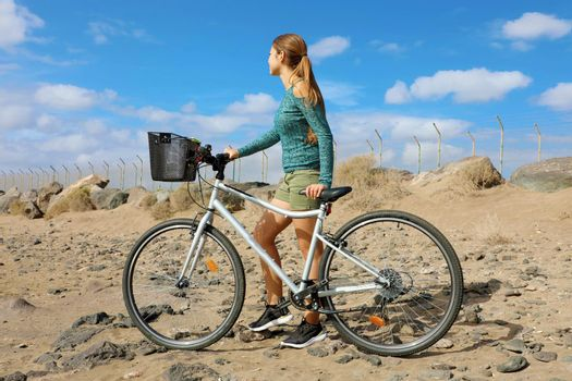 Adventure on bike. Back view portrait of young woman walking wit