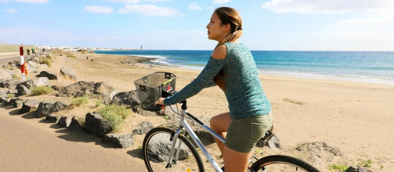 Panoramic banner view of young woman riding on bike in Lanzarote