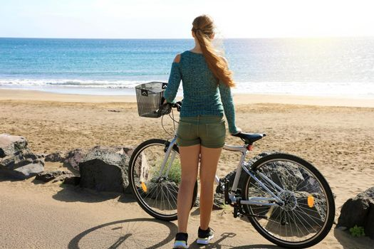 Young woman with bike stops to enjoying view of the ocean in Lan