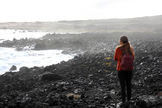 Desolate volcanic black rocks with lonely girl. Back view of young woman standing reflexive and sad on hidden rocky beach. Young female discovering wild black rocky beach in Lanzarote Island.