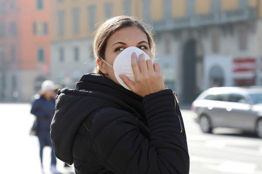 COVID-19 Woman in city street wearing face mask protective for spreading of disease virus SARS-CoV-2. Girl with surgical mask on face against Coronavirus Disease 2019.