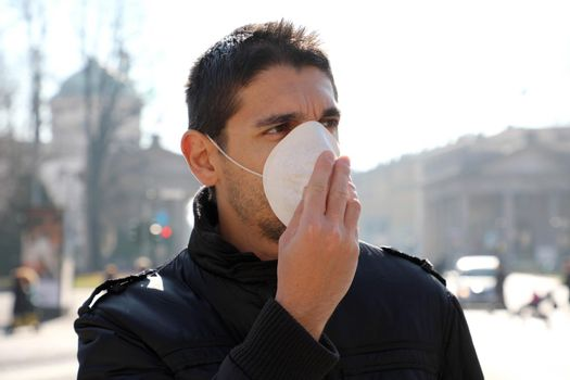 COVID-19 Man in city street wearing face mask protective for spreading of disease virus: Coronavirus Disease 2019. Close up man with surgical mask on face against SARS-CoV-2.