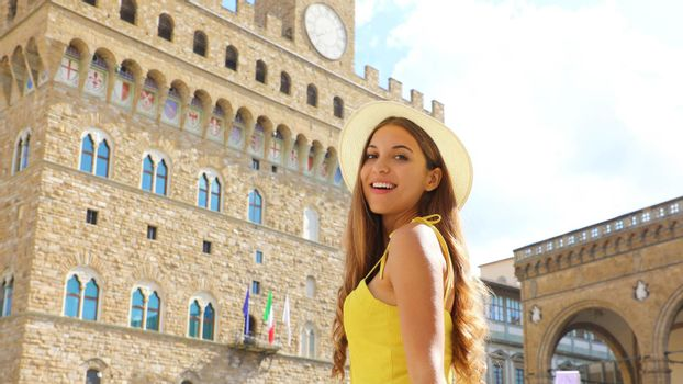 Beautiful tourist girl in Florence with Palazzo Vecchio palace
