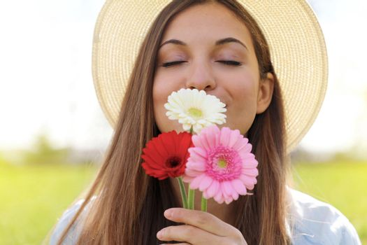 Teenager girl smelling the scent of flowers with hat and closed