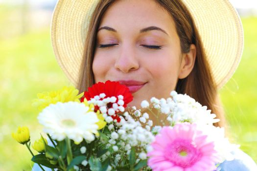 Close up of pretty girl smells and appreciates the scent of a bouquet of flowers just received