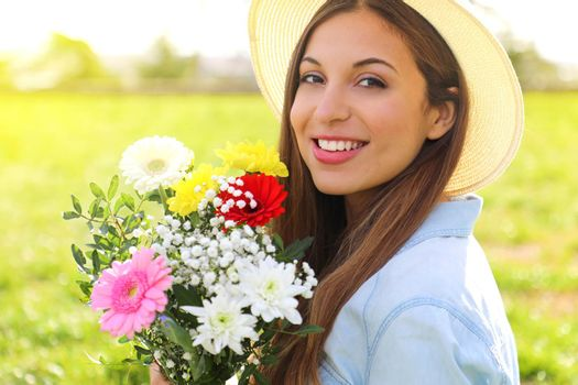Candid adorable young woman in field with flower bouquet at spring season