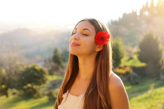 Relaxed young woman breathing fresh air with a green natural landscape on the background