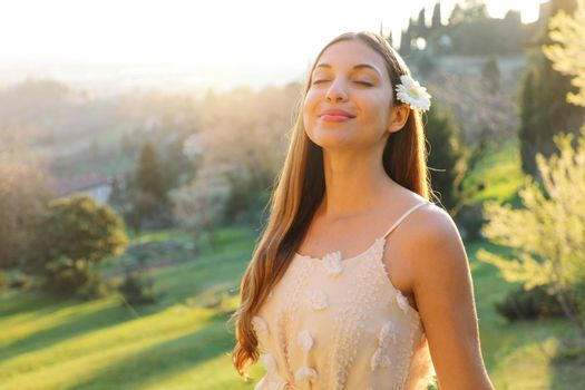 Purity and beauty concept. Portrait of beautiful girl breathing fresh air outdoor in nature with white dress and flower on ear smiling with closed eyes in spring summer time at sunset.