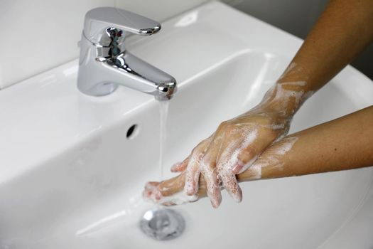 COVID-19 Hygiene concept. Washing hands with soap under the faucet with water against Novel coronavirus (2019-nCoV). Antiseptic, Hygiene and Healthcare concept.