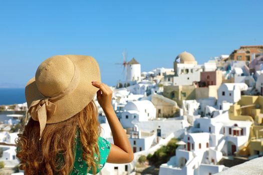 Holidays in Greece. Back view of young woman visiting Santorini island. Girl visiting the village of Oia in Santorini.