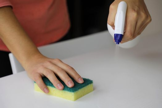 COVID-19 Pandemic Close up Woman hands disinfecting cleaning spraying bottle cleaner wiping down table surface preventive against SARS-CoV-2 Coronavirus disease 2019 outbreak contamination prevention