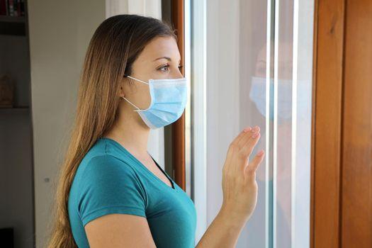 COVID-19 Pandemic Coronavirus Woman Quarantine Home Isolation Wearing Face Mask Against Disease Virus SARS-CoV-2. Girl looking through the window using mask against Coronavirus Disease 2019.