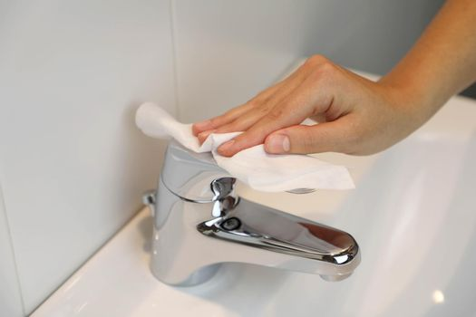 COVID-19 Pandemic Coronavirus Woman Hand Disinfect Faucet Sink with Wet Wipes Alcohol Cleaning Against Coronavirus Disease 2019 Outbreak Contamination Prevention