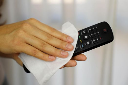 COVID-19 Pandemic Coronavirus Woman Cleaning with Wet Wipes TV Remote Control Disinfect Against Coronavirus Disease 2019 Outbreak Contamination Prevention.